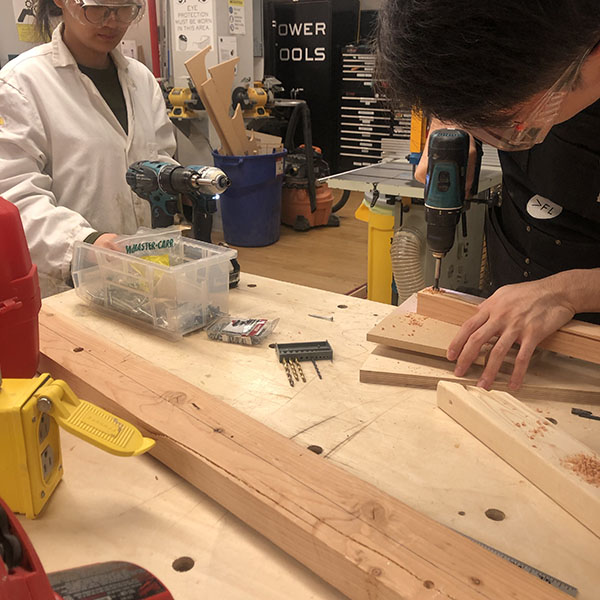 They're part of Team Scrappy, a team dedicated to imagining how folks in the apocalypse will re-purpose materials in order to build shelter and tools. The VFL has a full wood shop to help them get their prototype done