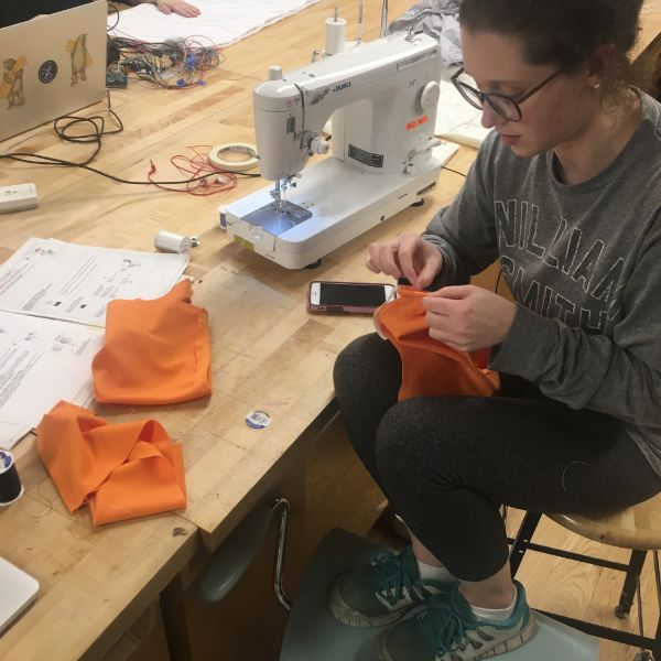 MFA Products of Design  second year Carly Simmons is in the lab today working on a nursing blouse for mothers in the workplace. She is using one of the shop's sewing machines and ancillary sewing supplies in order to modify an existing blouse with some knit fabric and elastic she sourced herself.