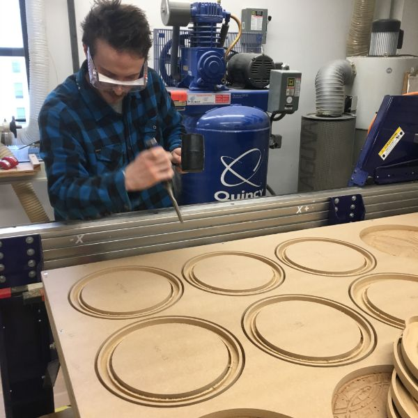 Second year  MFA Fine Arts  student is back in the shop working on his badge frames. He is using the  Shopbot  CNC router to create some variable thickness pieces.
