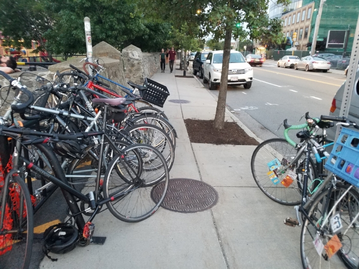 Inadequate amount of bike parking, evidenced by the dozens of bikes I saw nearby locked to street signs, trees, fences, etc. Poor placement of bike rack and unsuitable type of rack because it impedes sidewalk access.