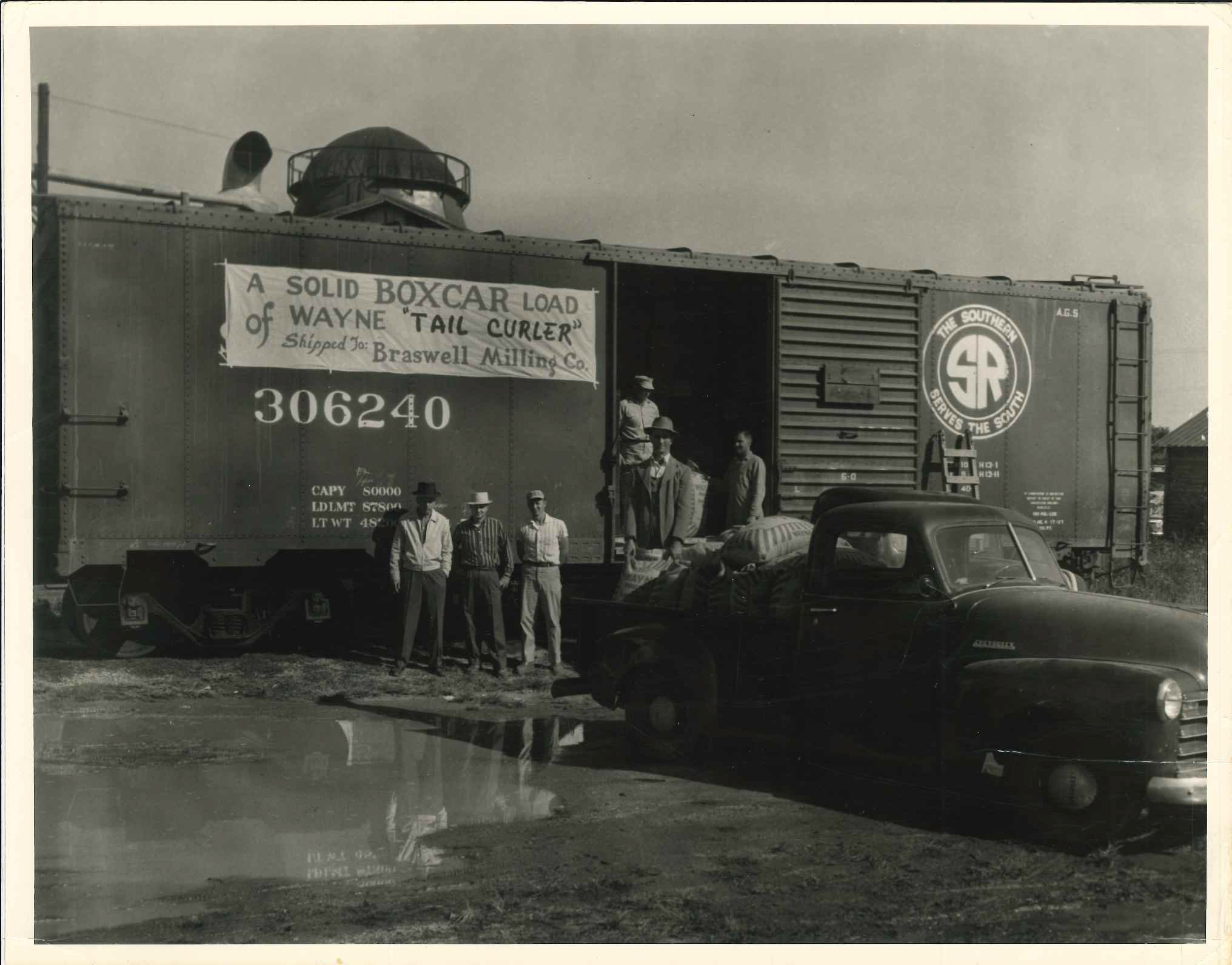 Ronald and Gene stand with a representative of Wayne Feed as they fill an entire boxcar with Wayne Tail Curler specialty swine feed from Braswell Milling.