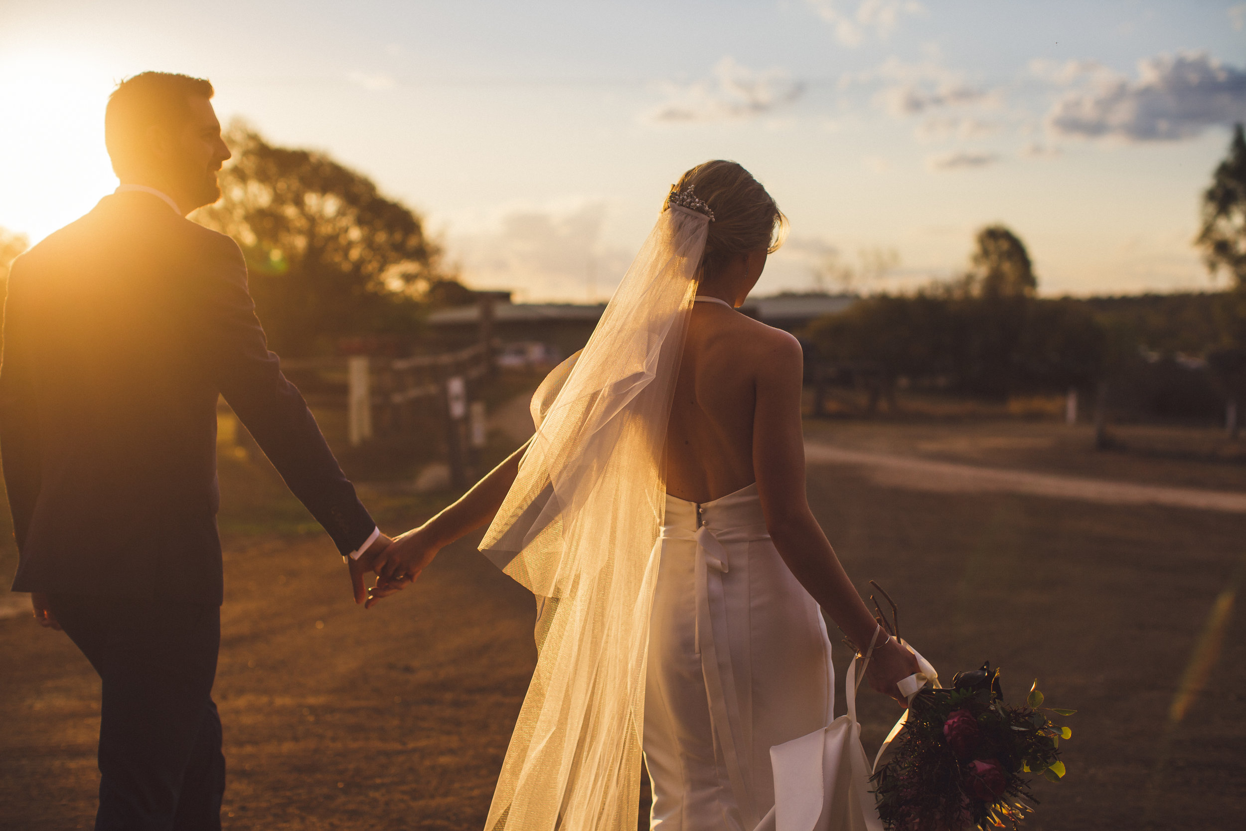 Bride and Groom holding hands at sunset at Spicers Hiddenvale