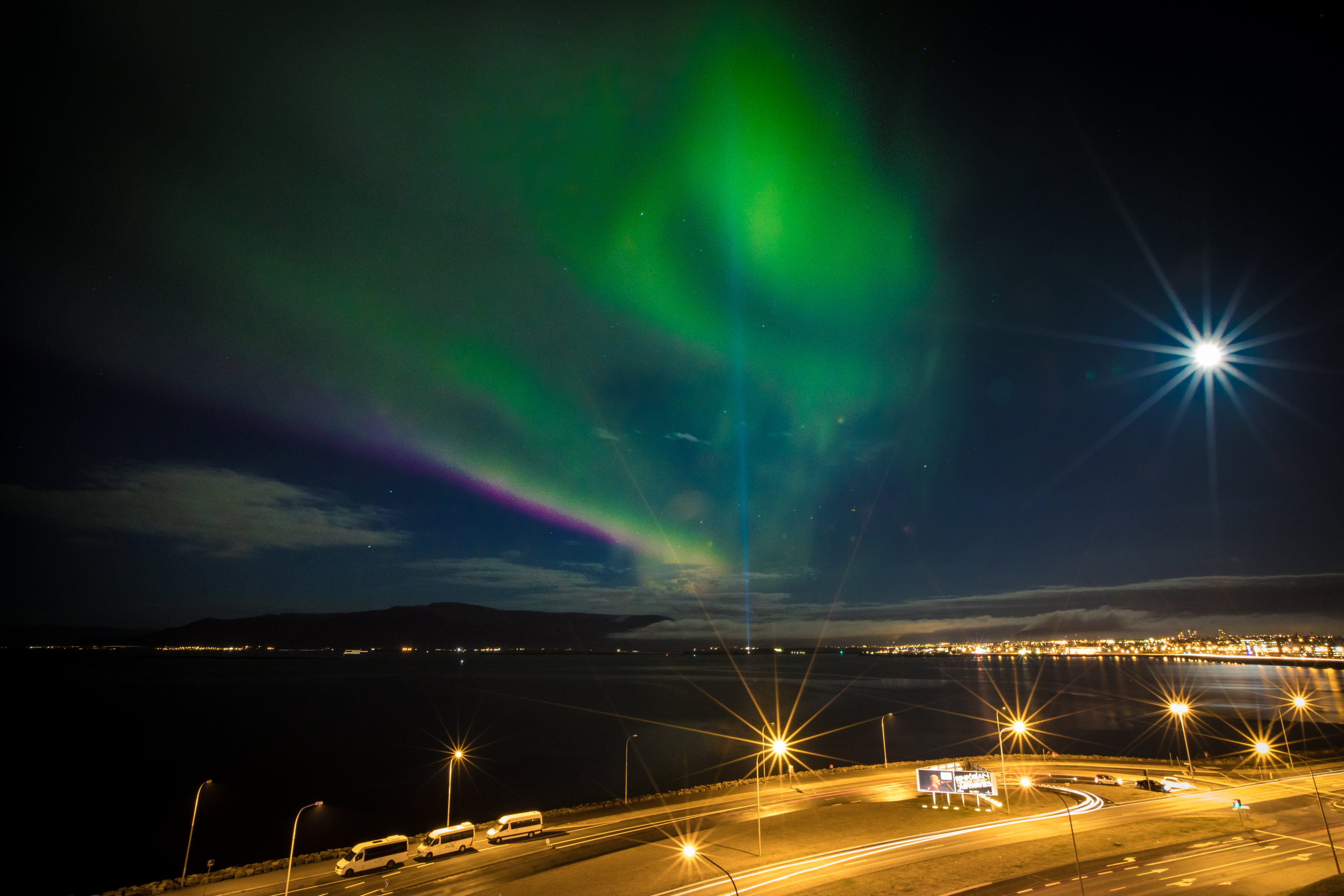 This shot was taken of the Northern Lights in Iceland. I used a 30 second shutter speed. You will notice at the bottom of the photo the car lights are continuous trails. Also, the Northern Lights are more of a blur of color rather than distinct light bands that you might see on other Northern Lights shots. Even with all the city lights and a full moon you can still see some stars at this setting.  Canon 5D Mark IV, 18mm | f/22, 30 seconds, ISO 100