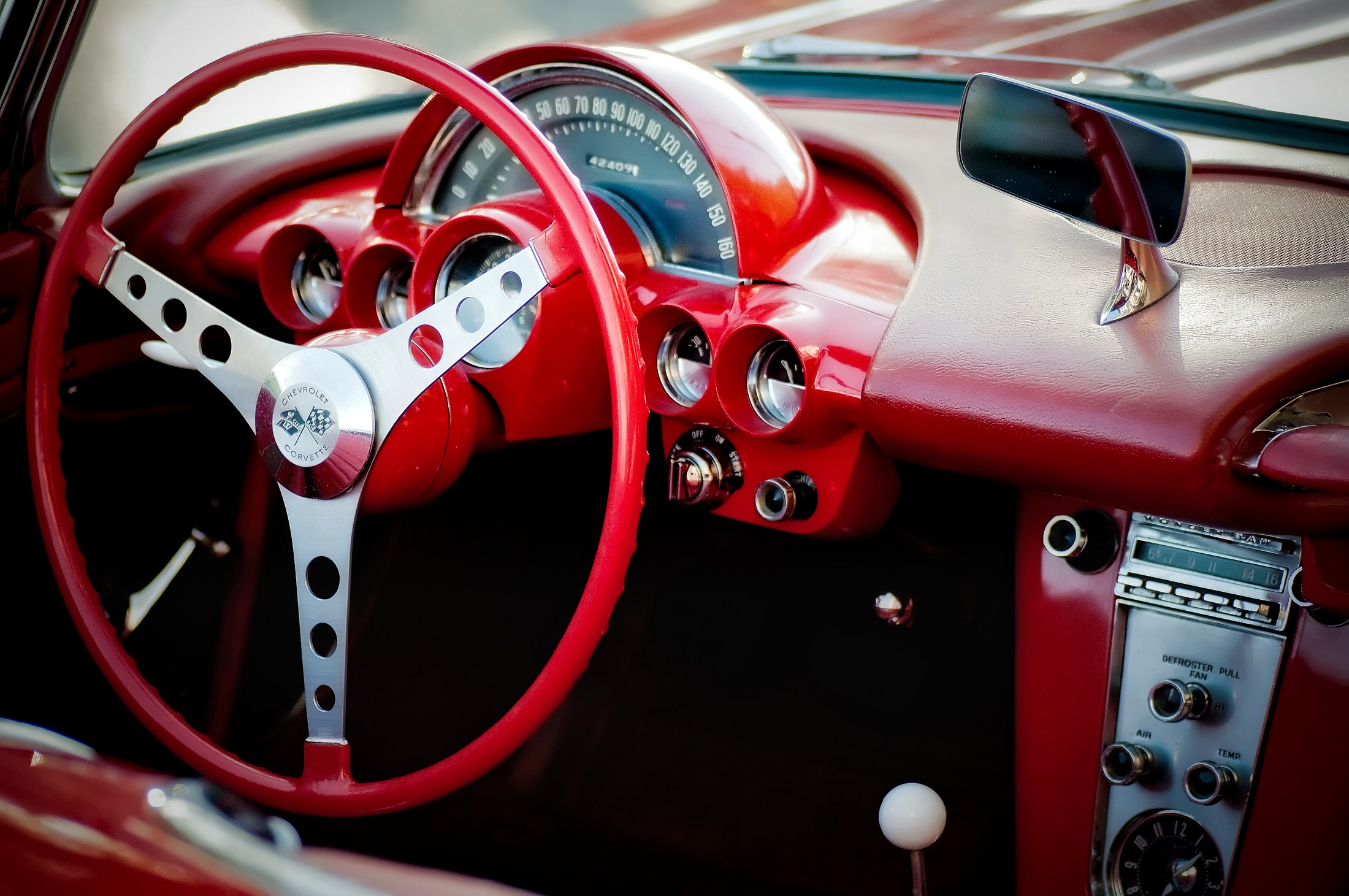 [iphoto of the steering wheel and dashboard of a red vintage sports car]