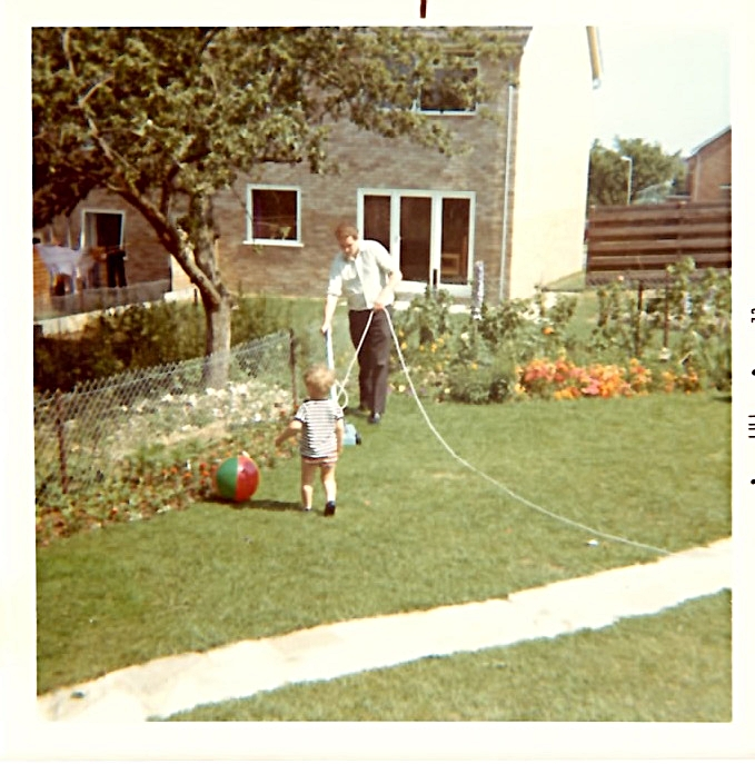 Dad watering the garden of our police house.