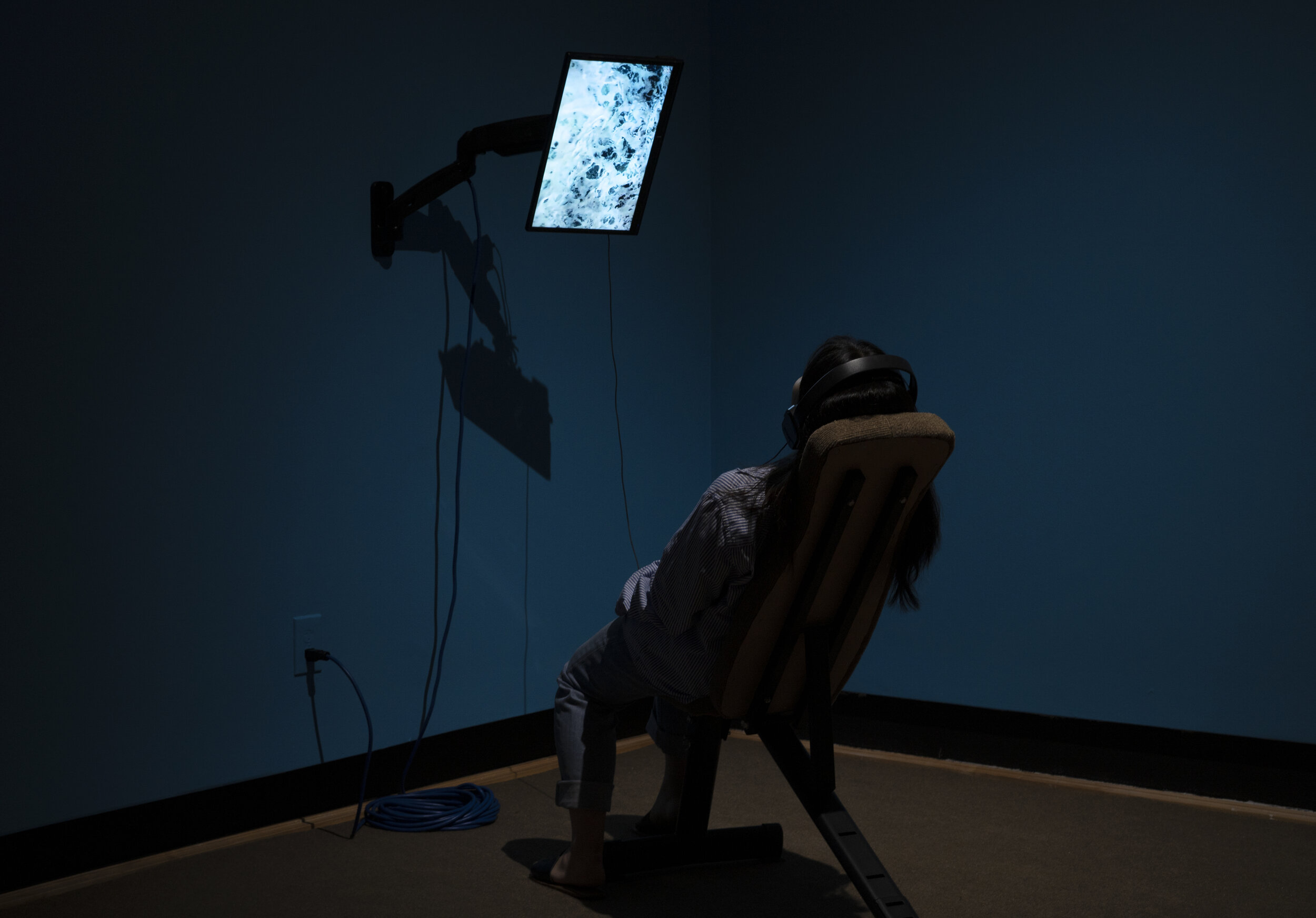 Pilgrimage to Hell and Back: A Guide to Disappearing and Resurrecting  (Installation view). Single-channel video, headphones, monitor, mount, extension cord, paint, carpet, incline bench. Dimensions variable. 2019