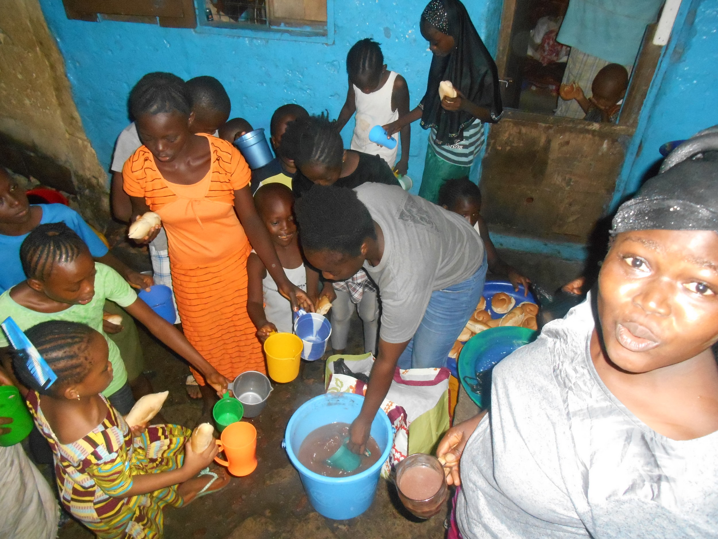 Aisha Koroma serving children hot chocolate in the same compound she was raised in Mountain Cutt, Freetown, Sierra Leone.