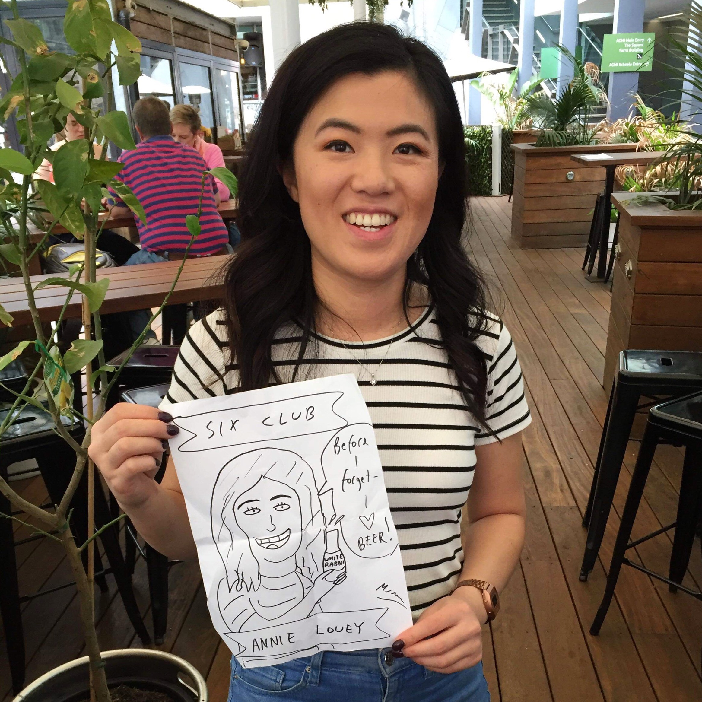 Annie holding a drawing of herself by fellow comedian Murphy McLachlan
