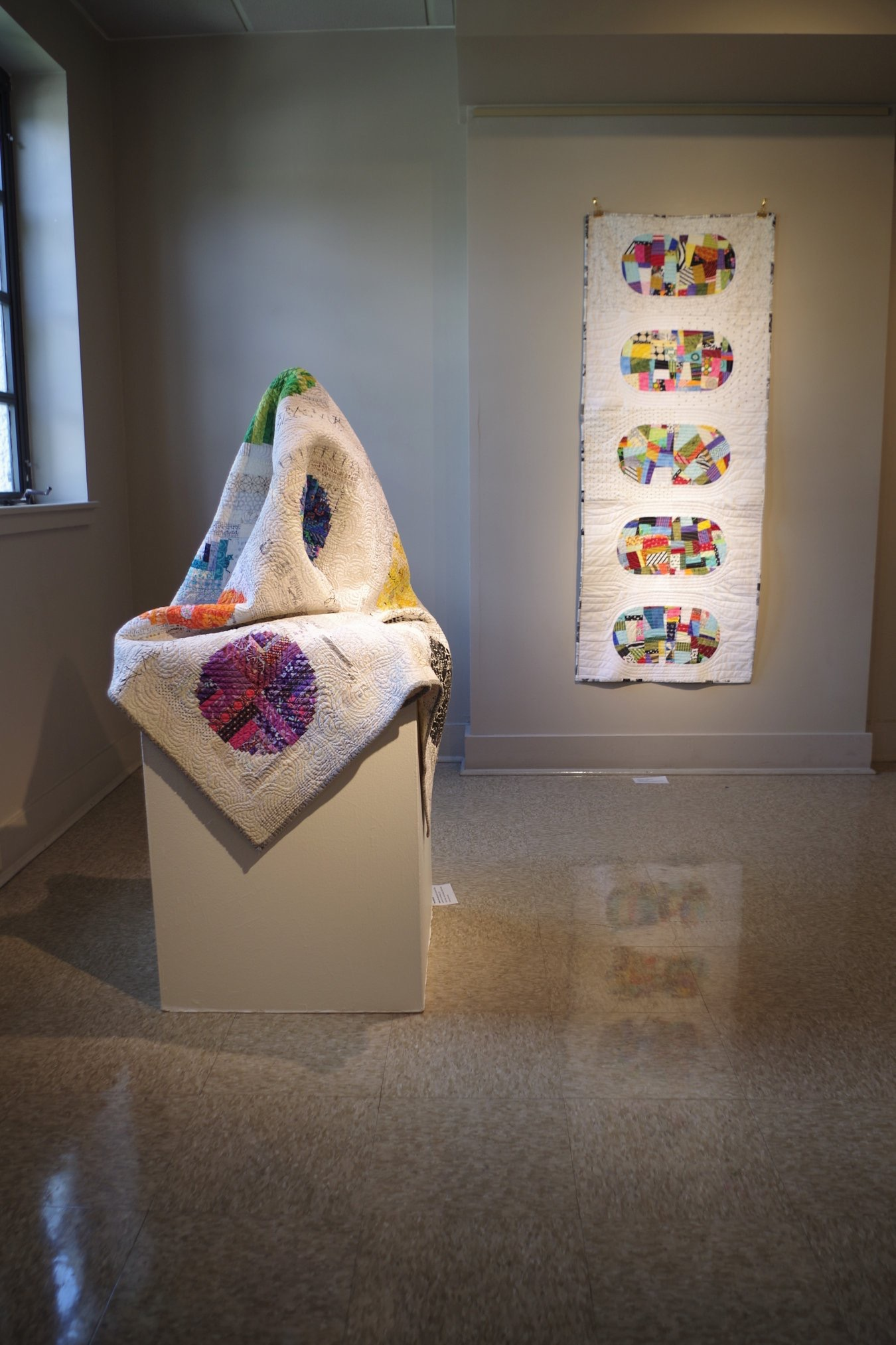 My quilt  being displayed as sculpture with  Sharleen 's beautiful quilt hanging on the wall.