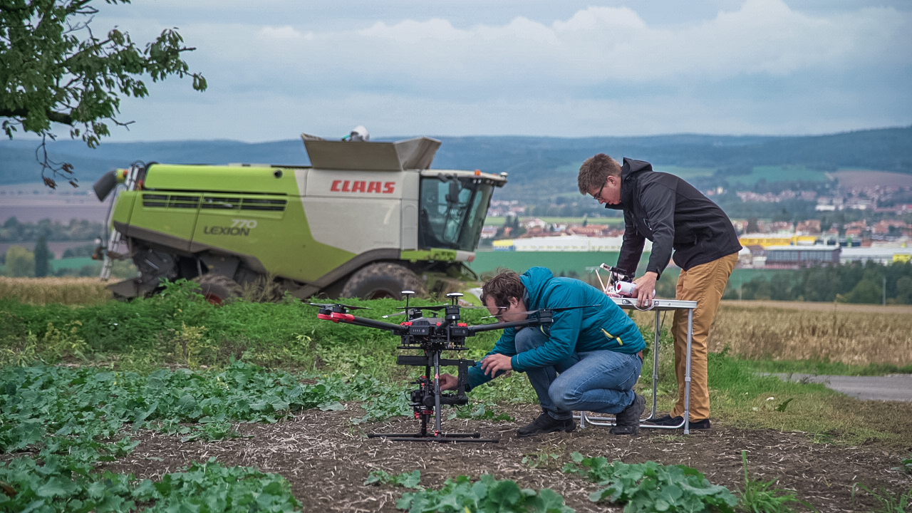 Agricultural drone with combine in the background
