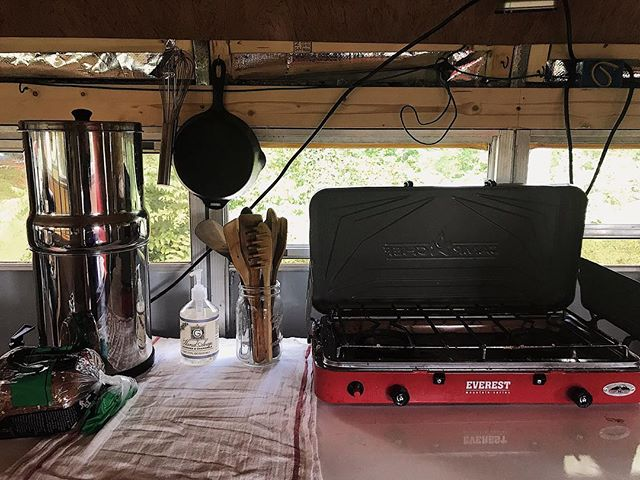 "Our humble kitchen! Living in our bus during a conversion hiatus means adjusting to the ""do with what you have"" mantra. We may not have cabinets and a built-in stove, but this @campchef does the job splendidly! And we can't imagine life with our @berkey_filters. 💧  That attitude, of making due and having gratitude, is quietly pervasive. It seeps into the way we see our own journey, our finances, our wardrobes, and our resources. All of us get bogged down in what we don't have, and it's easy to get wrapped up in the 'lacking' and pull back from life because we ""don't have"" what we want or think we need.  No day is perfect, but we're right where we are supposed to be.  Can you think of something you may be lacking, but a way to replace the absence with gratitude?  #schoolbusconversion #skoolie #tinyhouse #diyprojects #busconversion #buslifeadventure #buslifediaries #tinyhomeonwheels#tinyhomebuild #livingfreely #homeonwheels #rvrenovation #tinyliving #selfbuildcamper #homeiswhereyouparkit #motorhomelife #skoolieconversion #getoutstayout #takemoreadventures #outdoorliving #happyadventuring #weboughtabus #tinyhouseliving #adventuremobile #nomadiclife #livingsmall #offgridliving #campinglifestyle #welivetoexplore #busliving"
