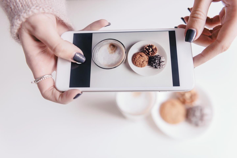 woman-taking-iphone-photo-cookies-coffee