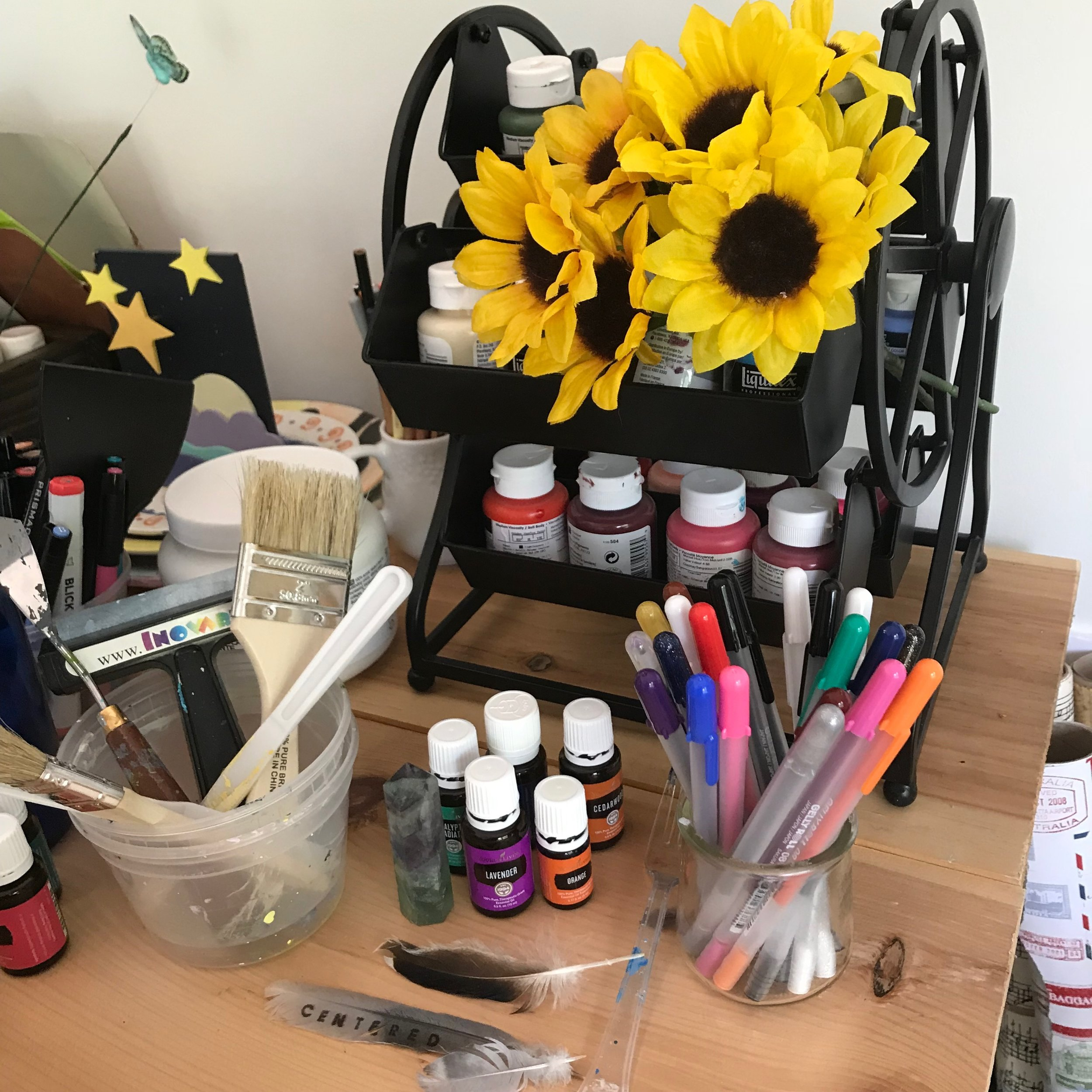 Feathers, oils, a crystal point, a paint carousel, a music box, some silk sunflowers, . . .