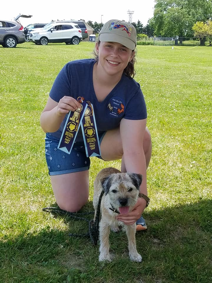 Blair and Keifer with his qualifying ribbons from the Fast CAT trial at the 2019 Border Terrier Club of America National Specialty.