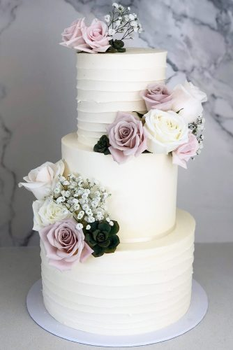 buttercream-wedding-cakes-classic-tall-white-with-lilac-roses-and-baby-breath-blondebakingmama-via-instagram-334x500.jpg