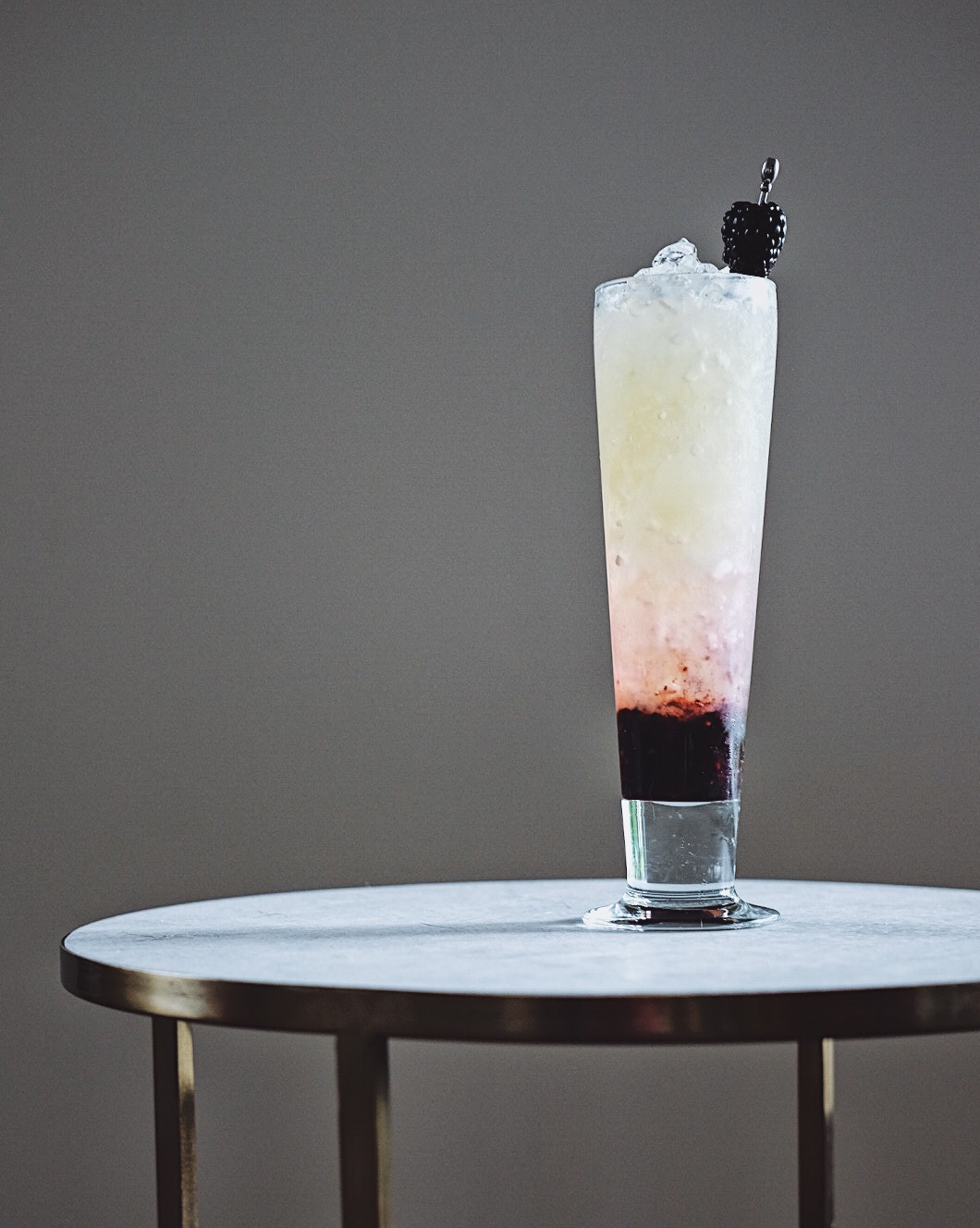 ingredients: - 2 oz silver rum3/4 oz fresh lemon juice1/2 ginger syrup1/2 oz orgeat1/4 oz honey syrup3 blackberriesPeychaud's bittersGarnish: skewered blackberry