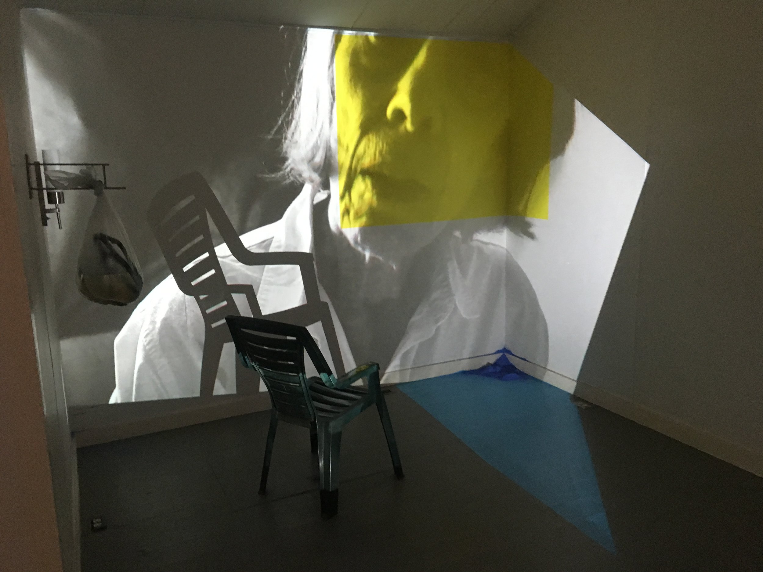 Yellow for Joan,  installation view at MacDowell Colony, projection, chair, goldenrod, paint, chalk, dimensions variable, 2019.