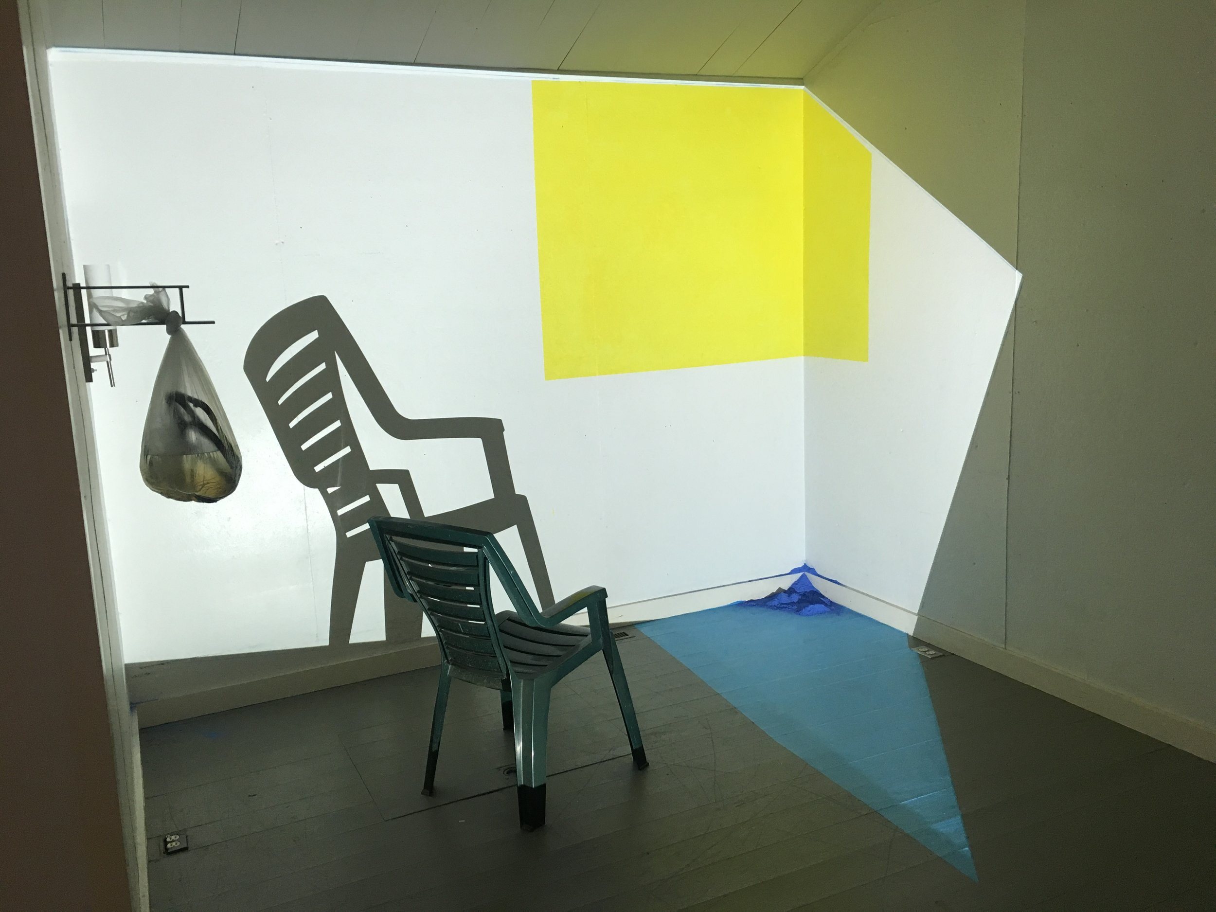 Yellow for Joan,  installation view when projected image turns off for a brief period and reveals the structure behind the image, at MacDowell Colony, projection, chair, goldenrod, paint, chalk, dimensions variable, 2019.