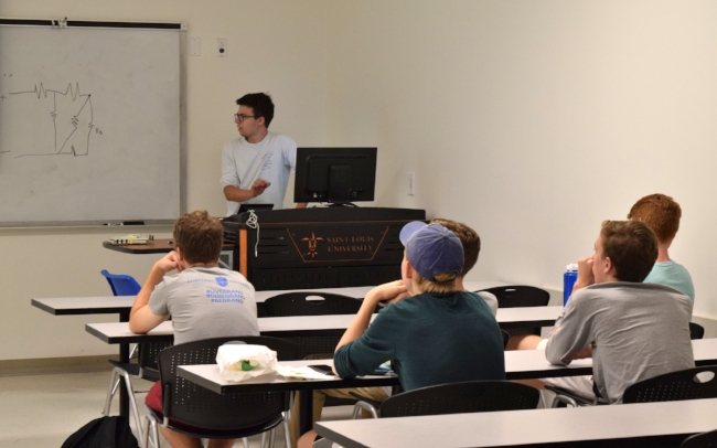 Here, Matthew Boss gives new lab members an introduction to electrical engineering and circuits.