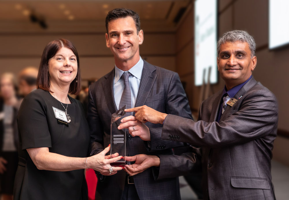 Jeff Aronin receives Northern Illinois University's 2019 Innovation and Entrepreneurship Award, presented by Dr. Lisa Freeman, President of NIU, and Dr. Balaji Rajagopalan, Dean of the College of Business.