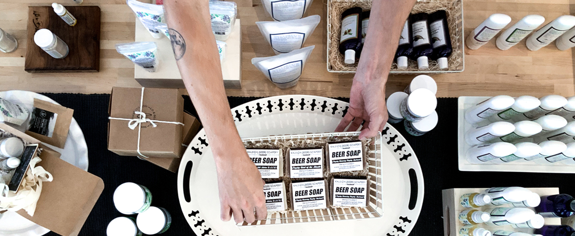 Arranging Raleigh Beer Soap on a display table at Raleigh Provisions Local Store