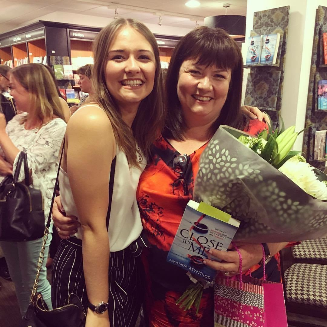 Happy with flowers and book in hand after the signing