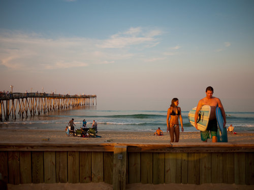 USA. Kill Devil Hills, North Carolina. 2010. A couple packs up after a day of summer surfing near the Avalon Pier. The biggest swells won't arrive until fall. Since the '60s, when surfing made its way here, the sport has steadily become embedded in OBX culture, and pros from around the world come to sample the waves.