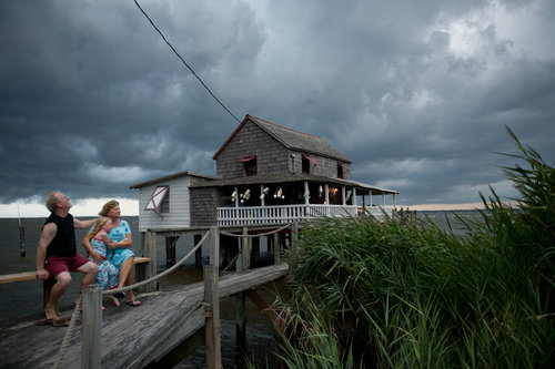 USA. Nags Head, North Carolina. 2010. My neighbors Billy and Sandra Stinson watch a squall roll over their house on Roanoke Sound. Hurricane Irene destroyed the place last August.