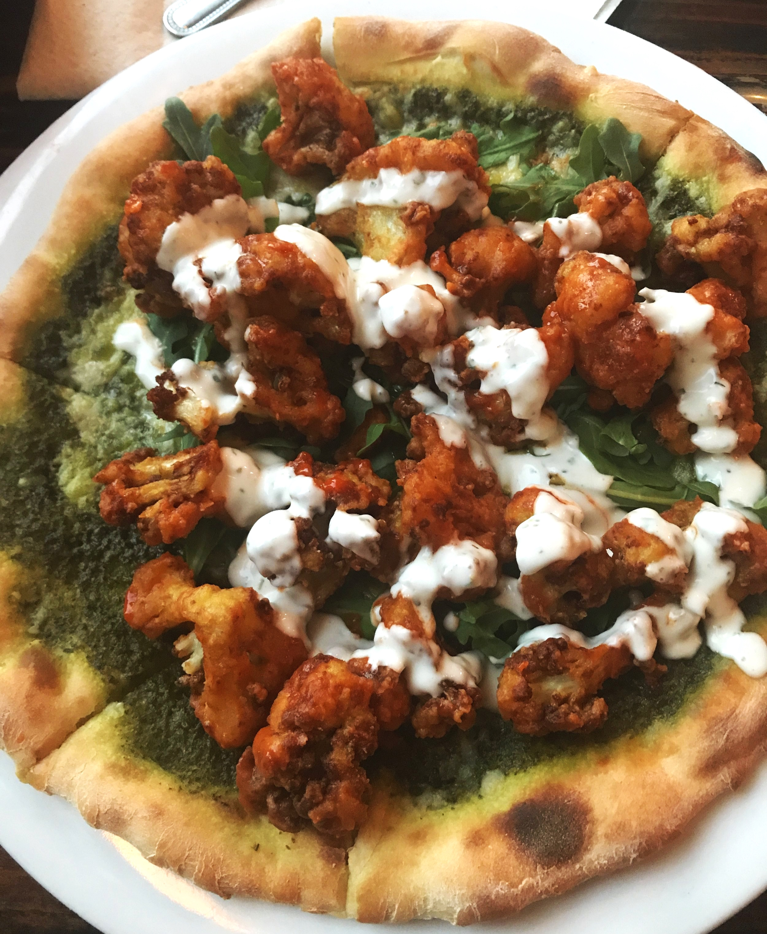 Sage Vegan Bistro's  Pesto Buffalo Cauliflower pizza topped with vegan ranch and arugula. YUM