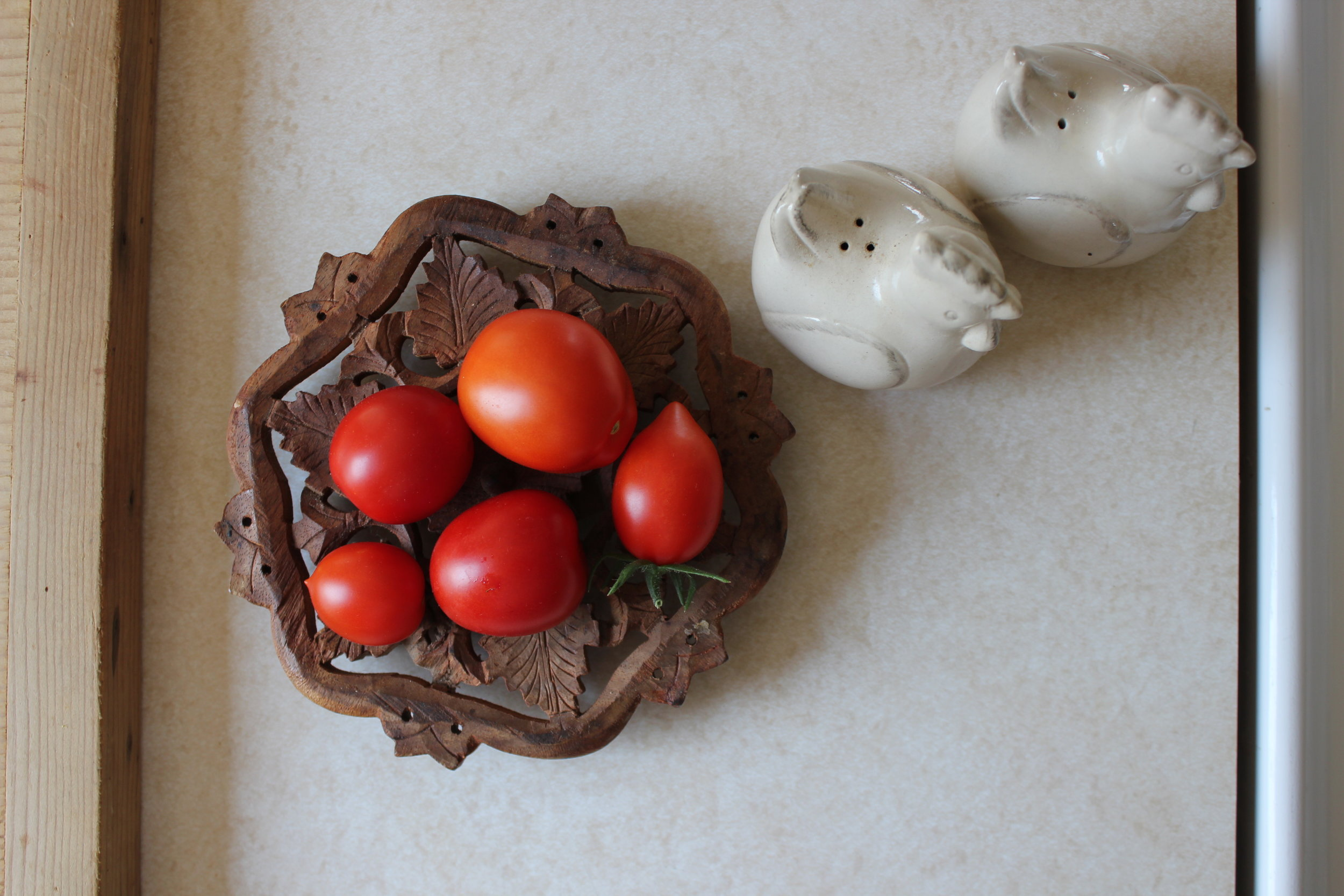fresh tomatoes and rooster shakers at farm house.JPG