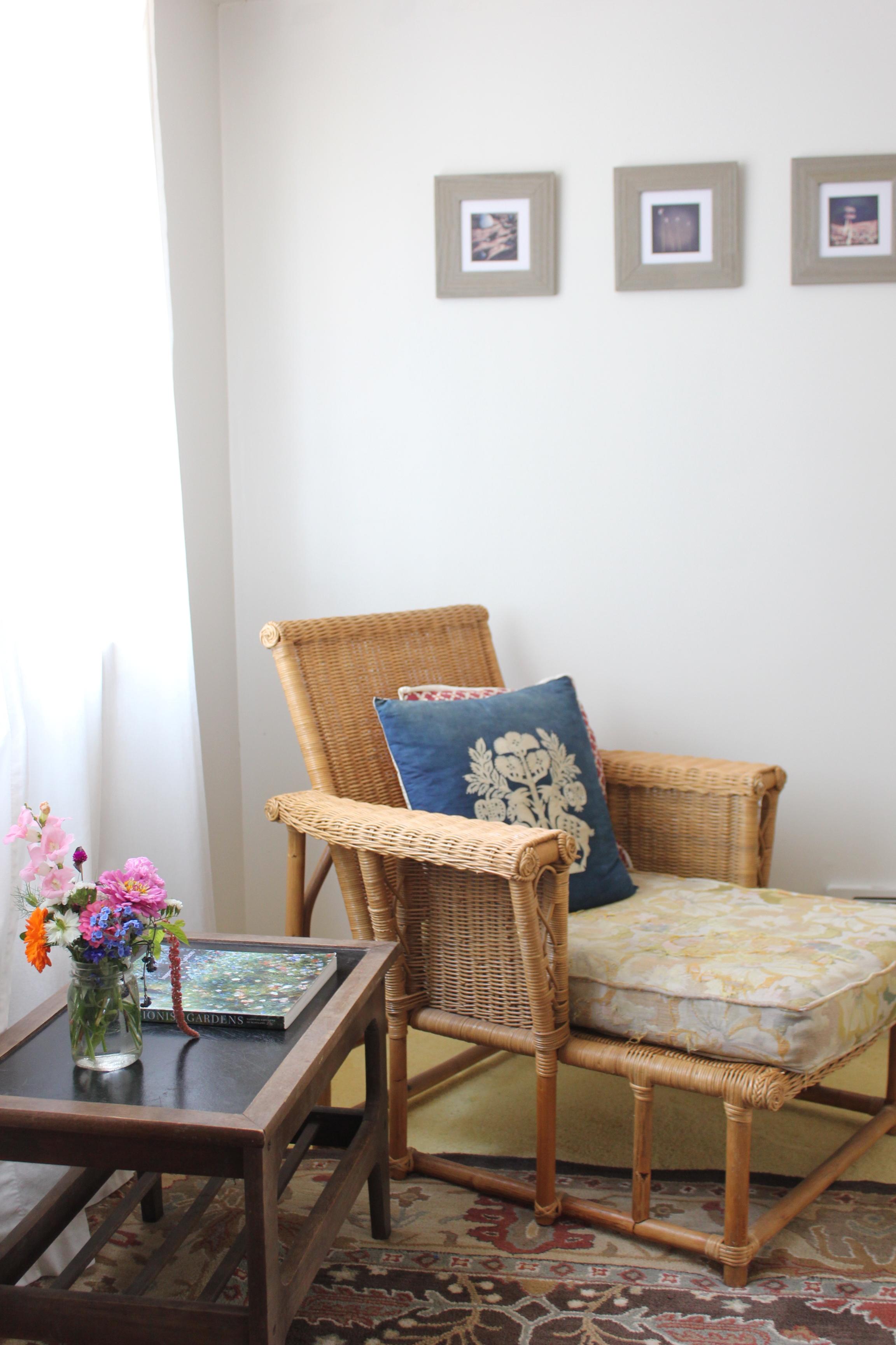 rattan recliner and fresh flowers at plum nelli farm chic airbnb.JPG