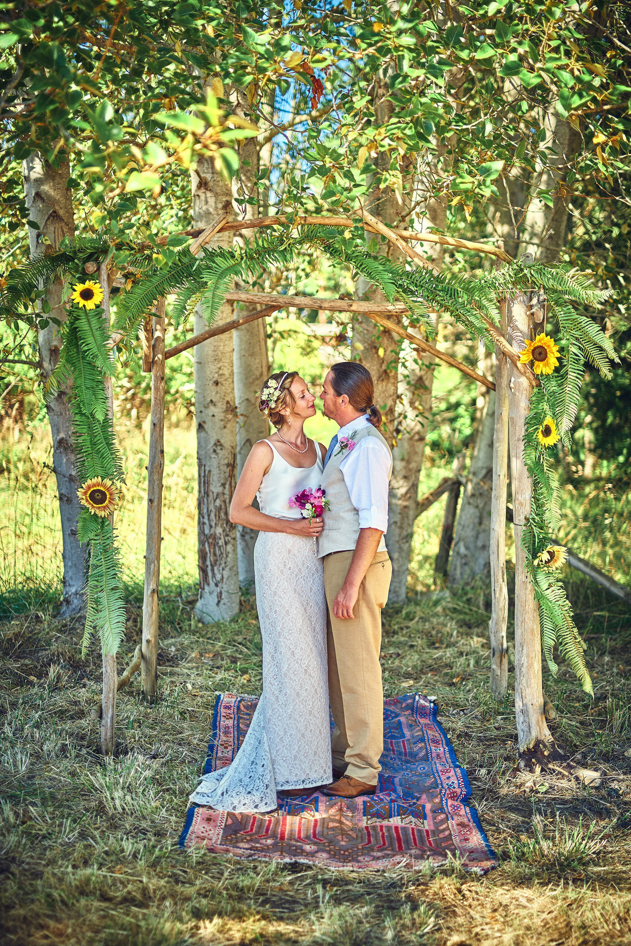 plum nelli farm wedding arbor with ferns and sunflowers and woven rug.jpg