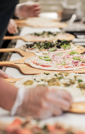 Unfinished pizzas on an assembly line
