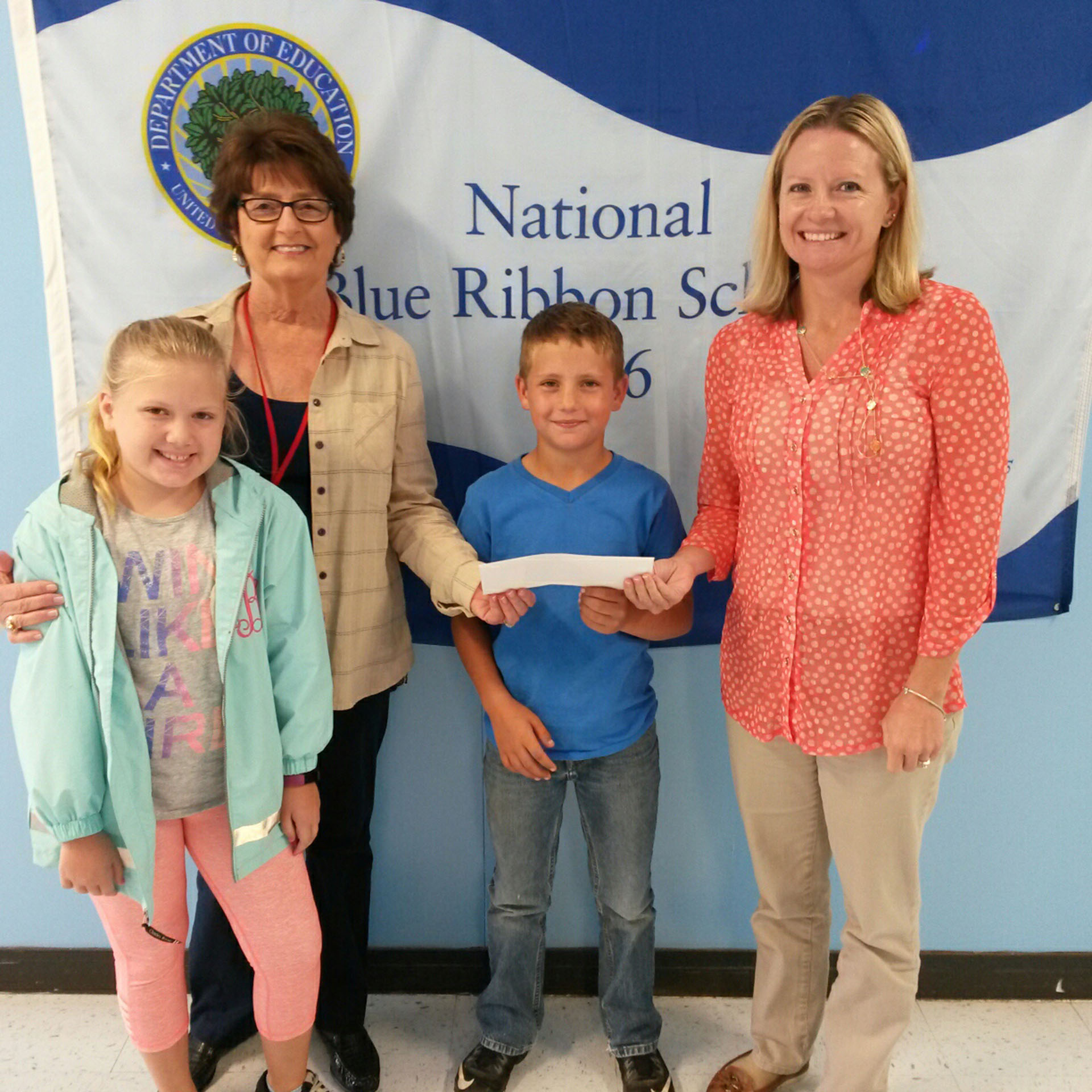Jodi Butler, Principal of Southwest Calloway Elementary, receives a check from Luna Greer, Calloway County Retired Teachers association. Students Kendall Brewer and Jack Kelso look on.