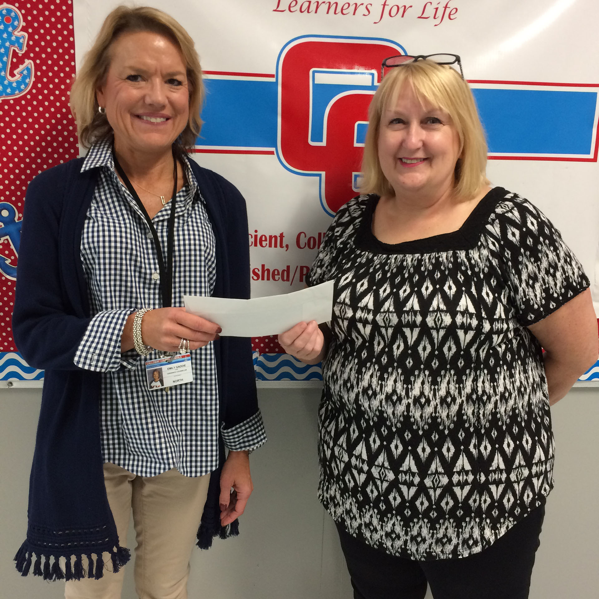 Emily Gaddis, Guidance Counselor at North Calloway Elementary, receives a check from Sandy Anderson President Elect of the CCRTA.