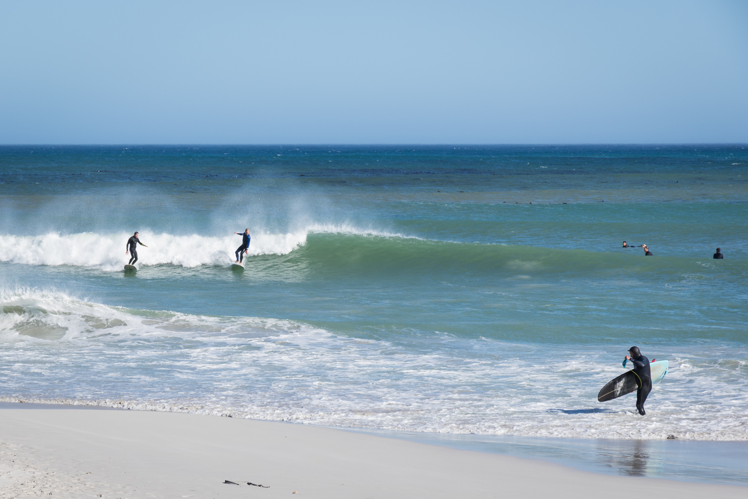 surfers riding waves in cape town