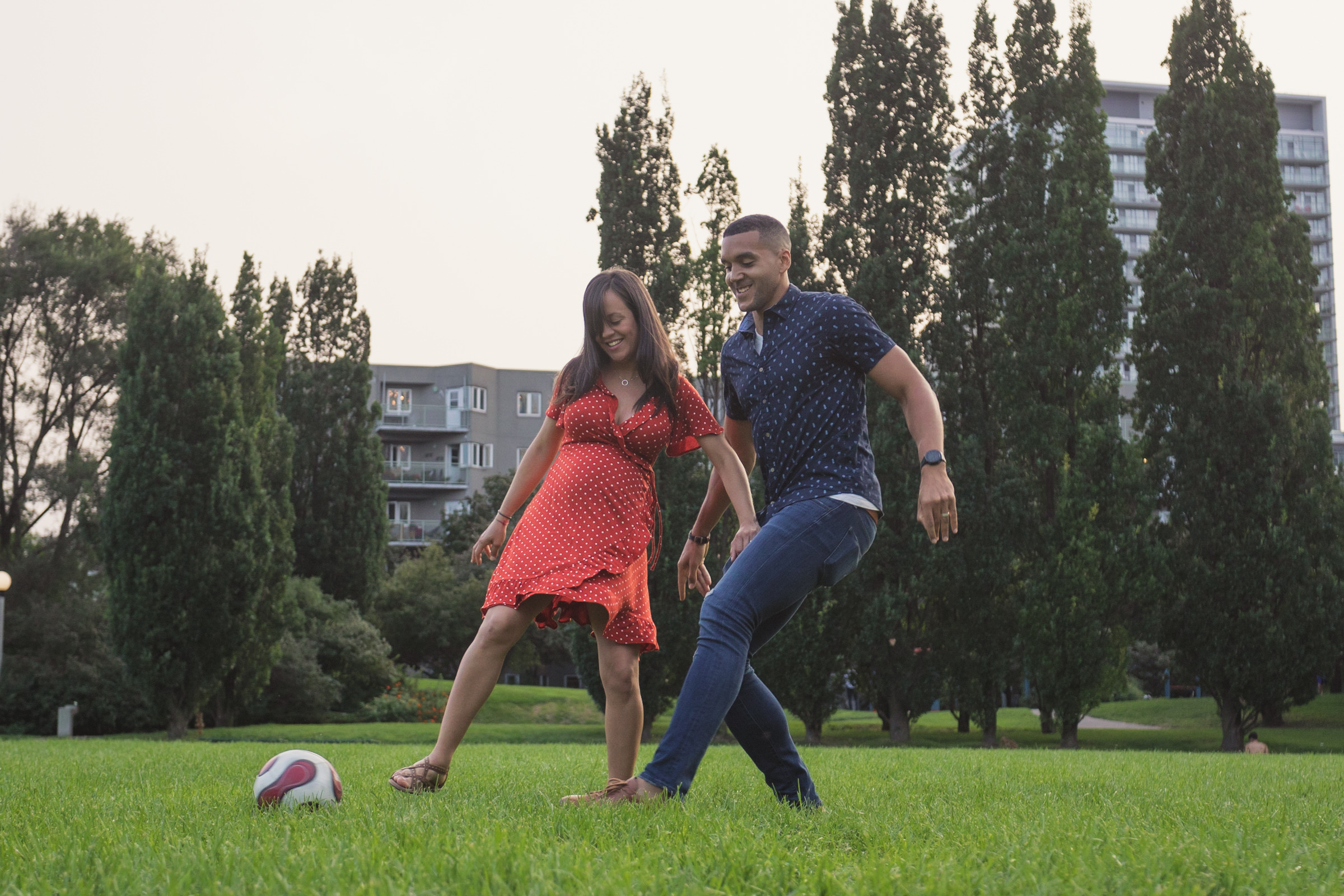 pregnant couple playing soccer together outside