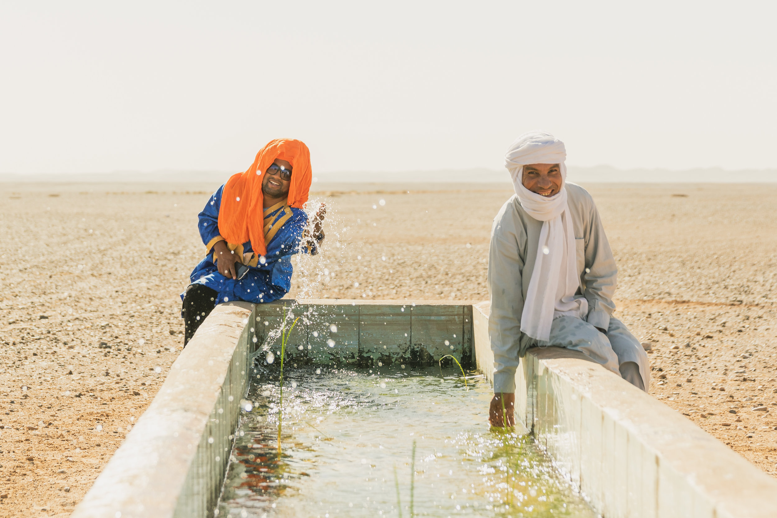 two moroccan tour guides splashing water in the Sahara desert