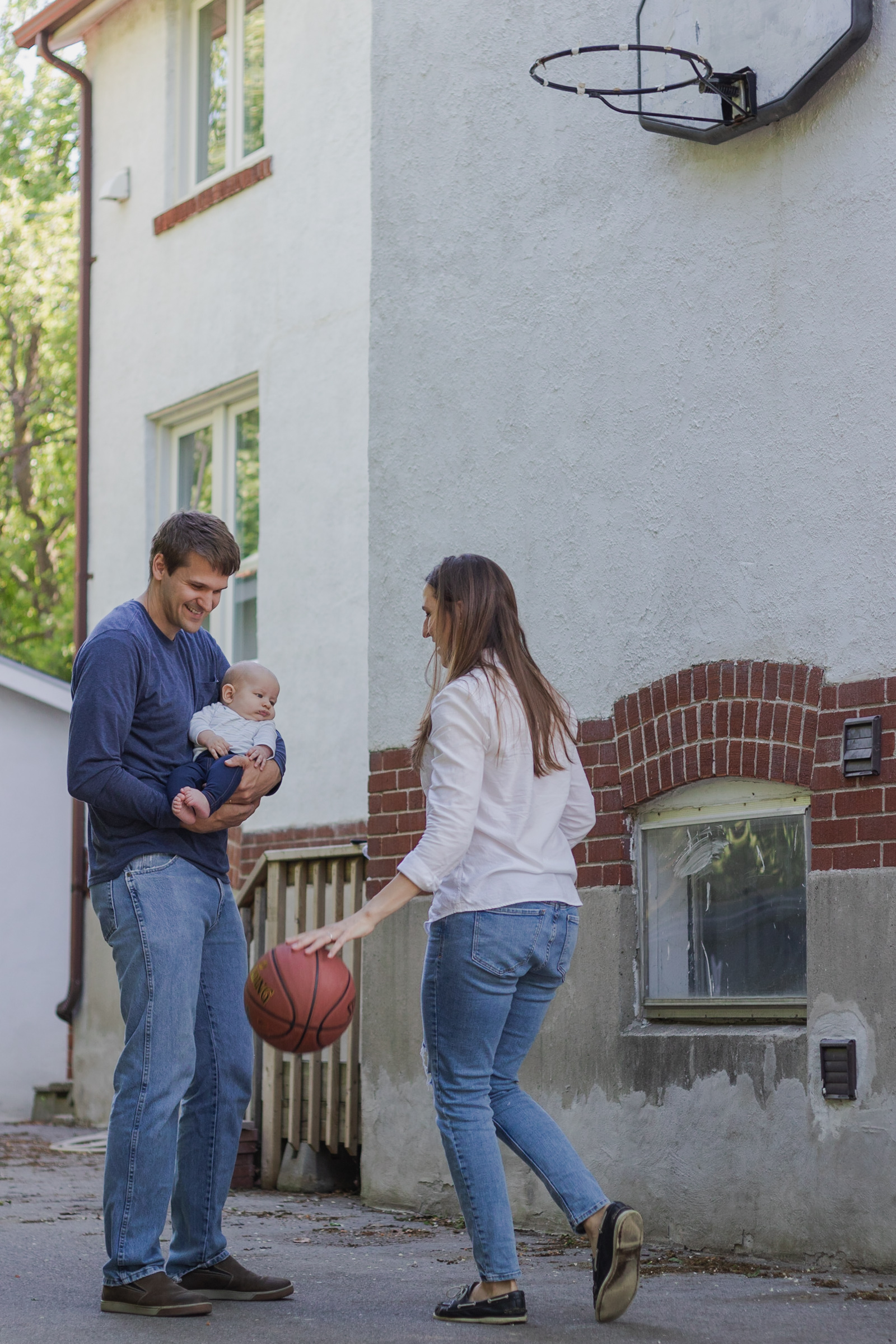 young family playing basketball together in their front yard