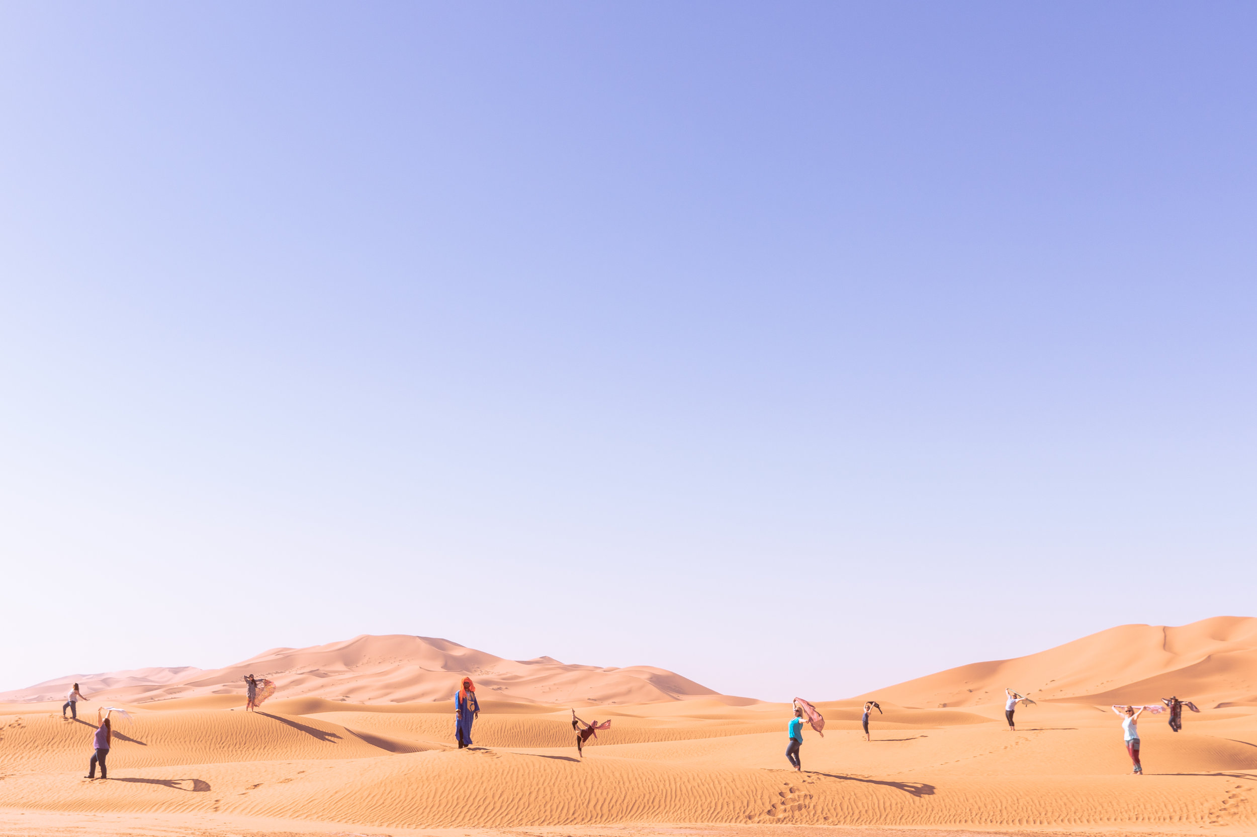 group of female travellers posing for a group picture in the sahara