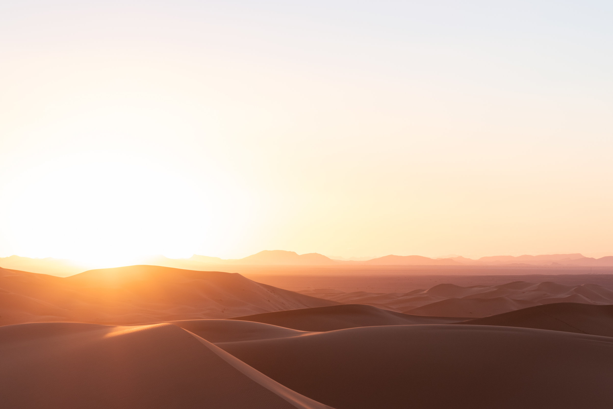 view of the sunset in the sahara from the top of a sand dune