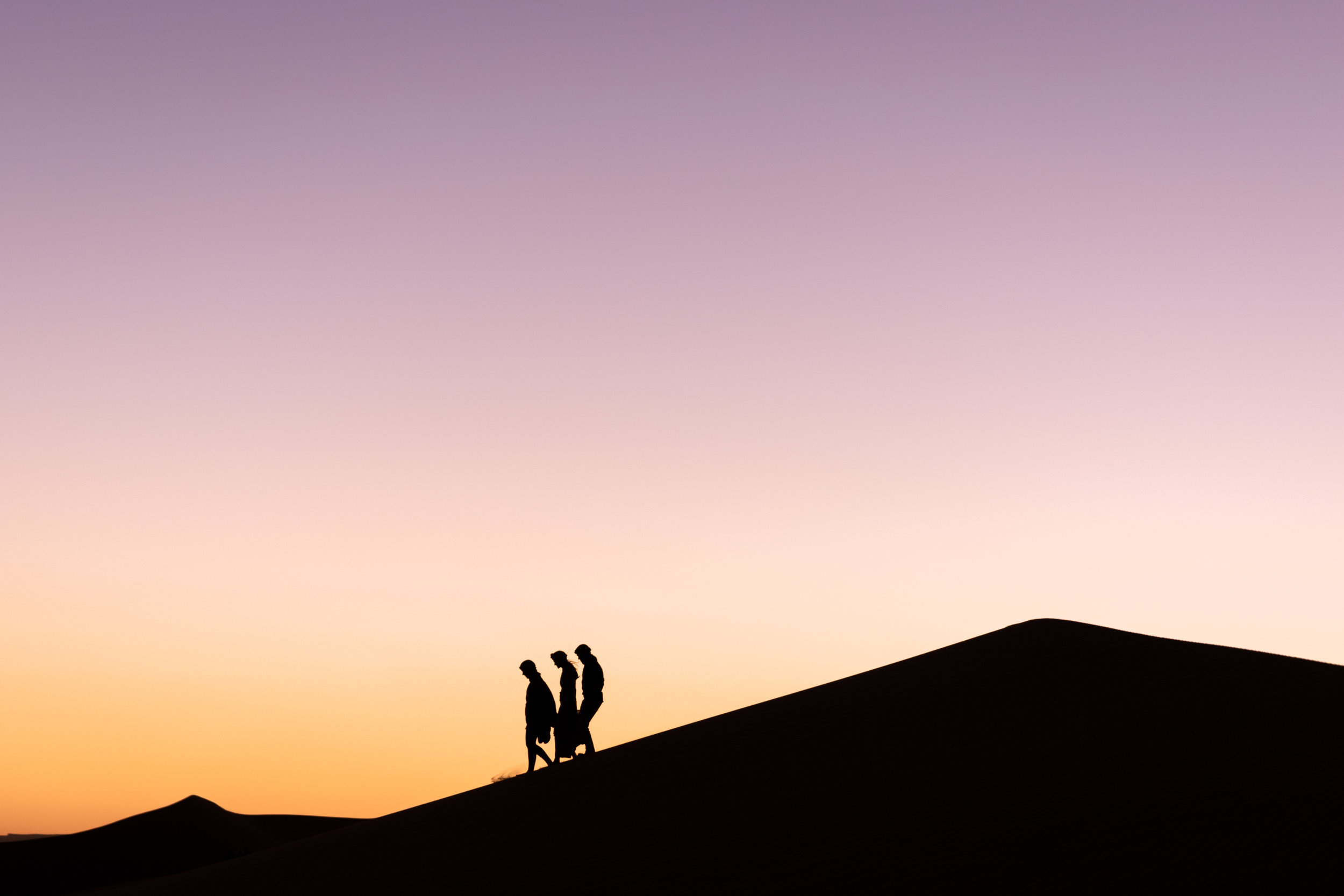 silhouette of three hikers at sunset in the sahara