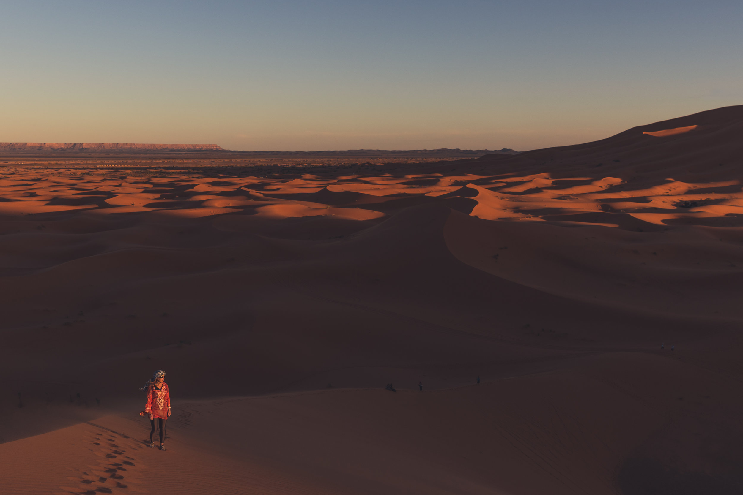 female hiker taking in the sunset during a hike in the sahara