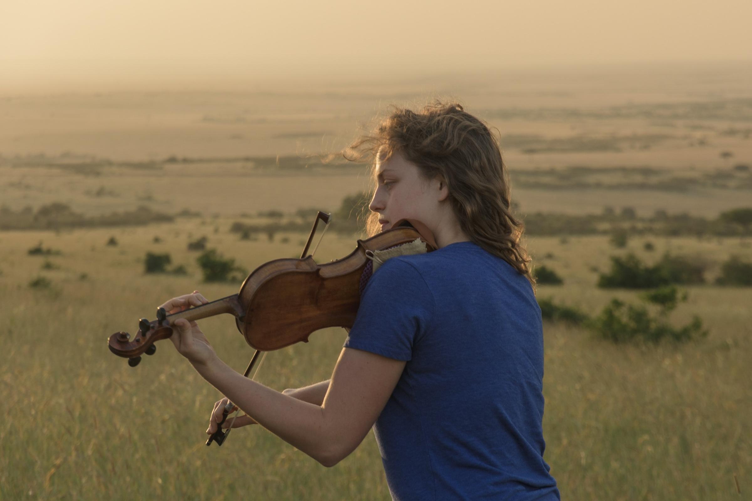 female playing violin at sunset in Masai mara reserve