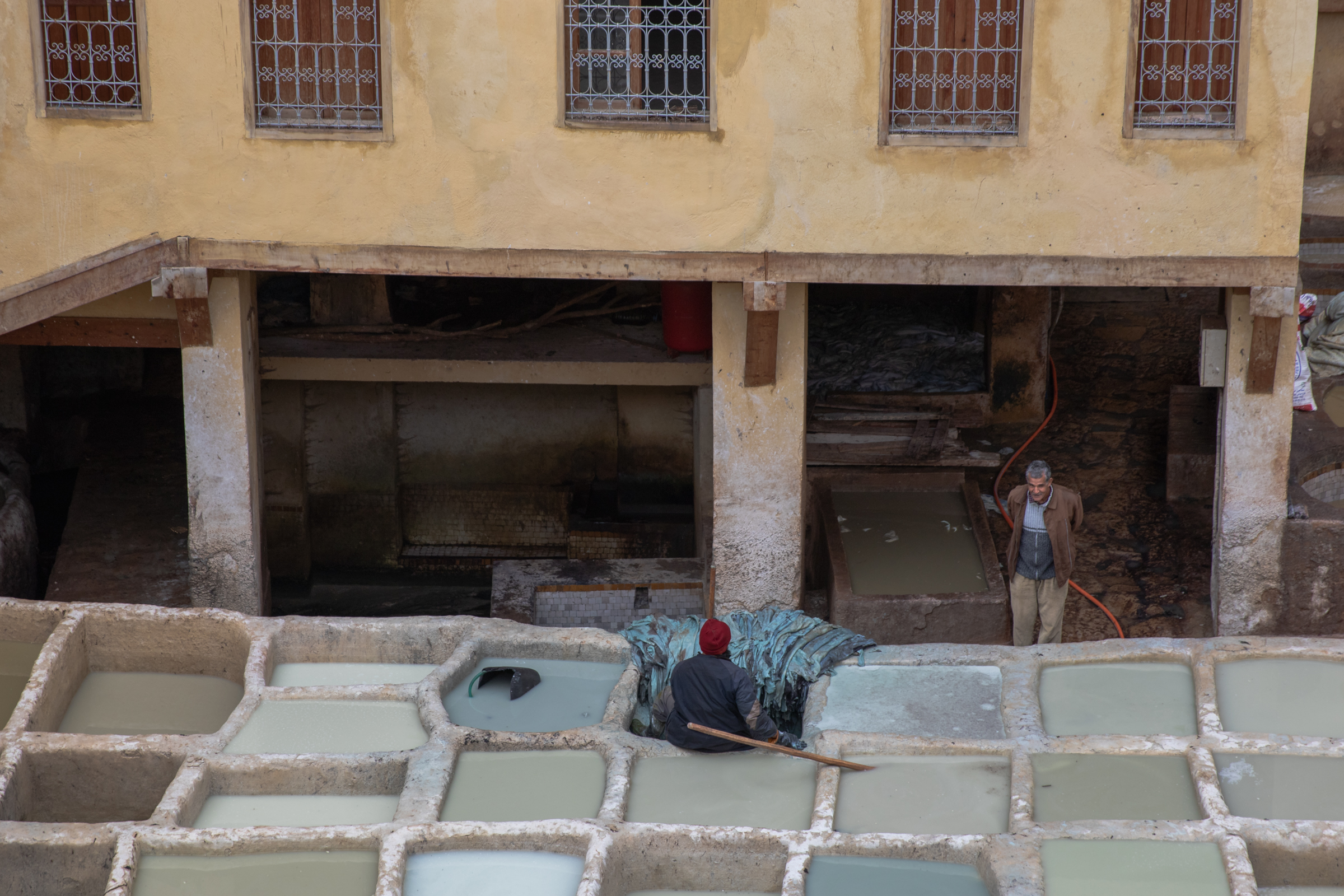 two moroccan men chatting at a leather tannery in fez