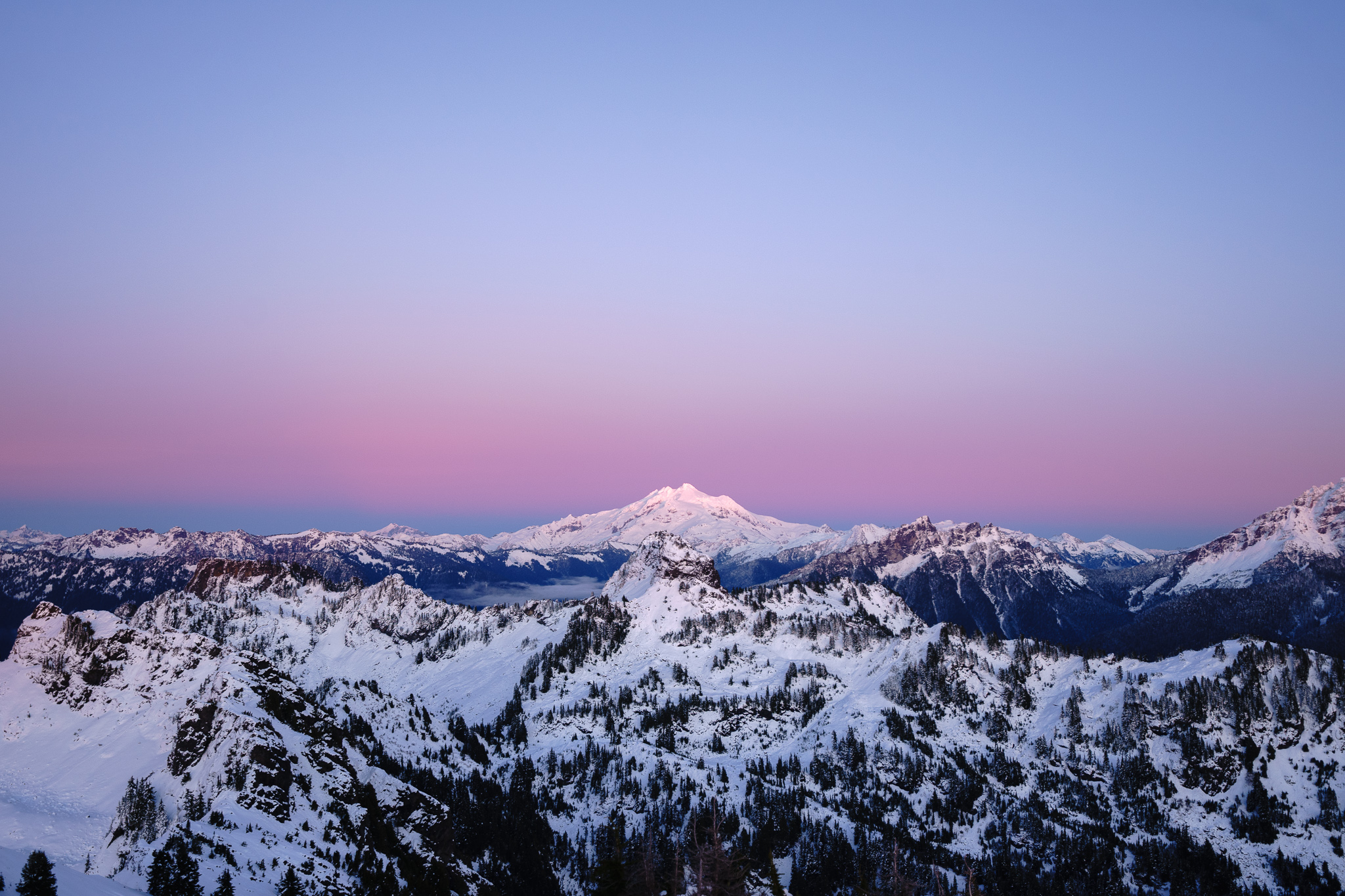 Glacier Peak lit up with the bright pink of the sky