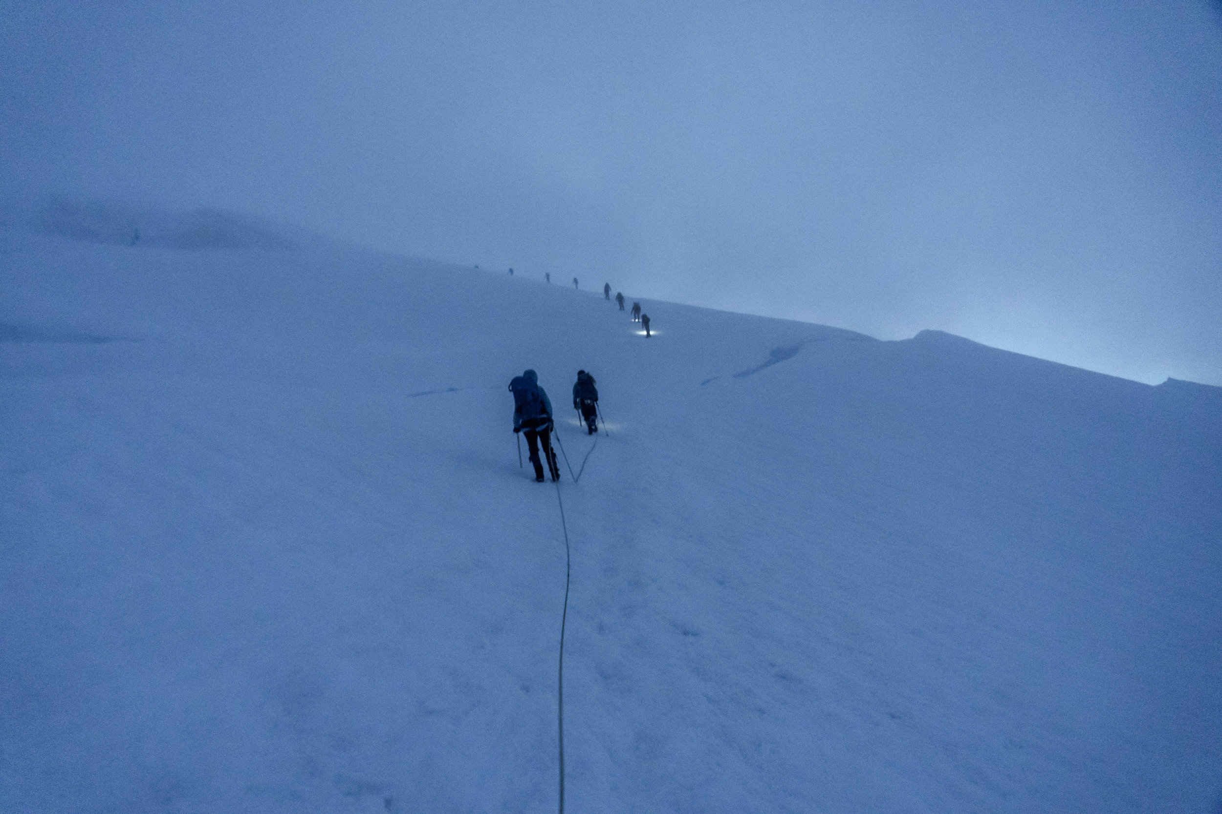 Climbers in the night with crevasses in the distance