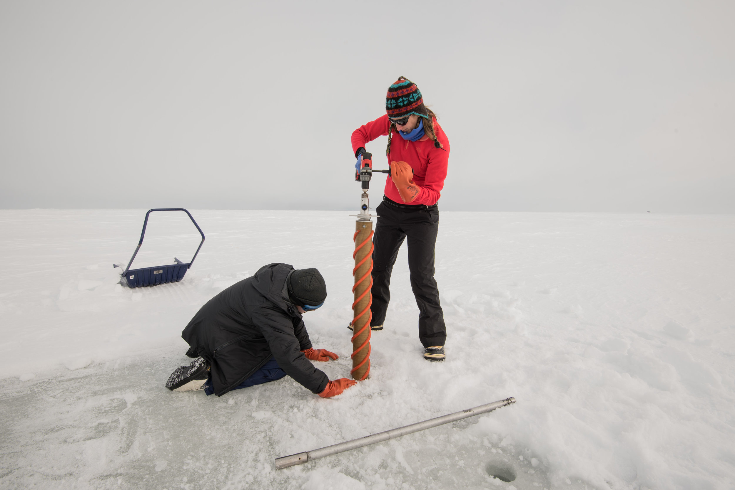 Jodi Young and Hannah Dawson drilling through some sea ice. Photo credit: A. Torstensson