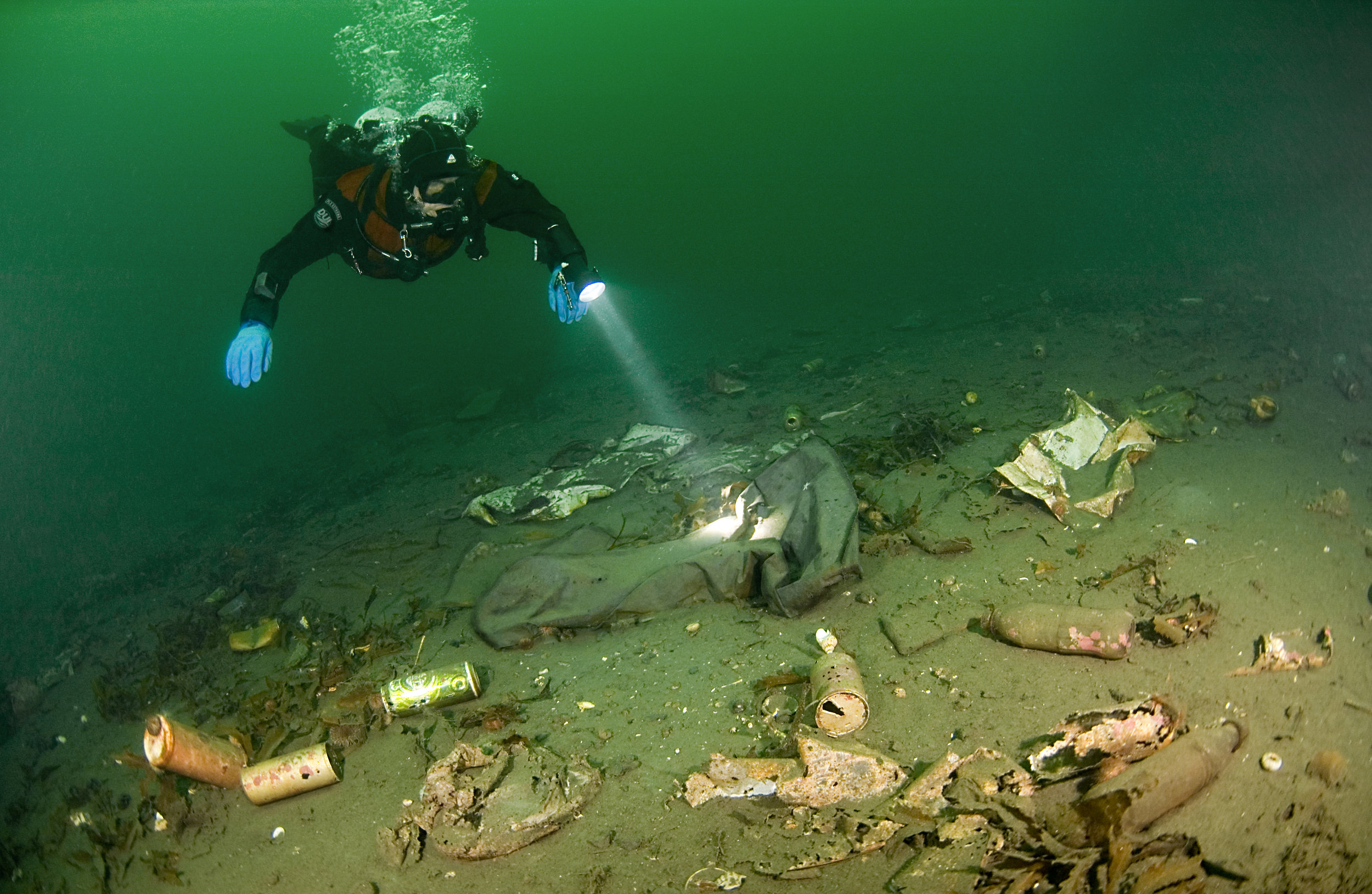 A diver shines a light on underwater pollution. Photo by:Fredrik Myhre / WWF-Norway