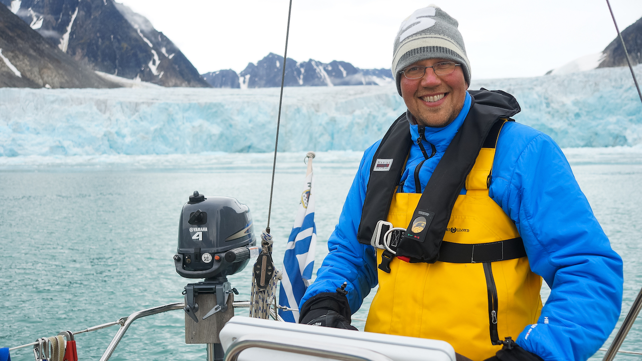 Ruffe onboard his 30 ft Bavaria in front of one of many glaciers in Svalbard. Photo by: Kari Nurmi